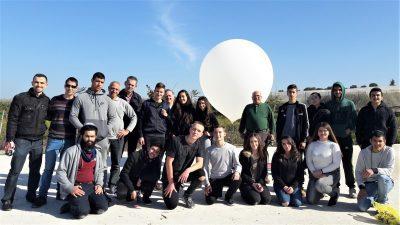 תלמידי תכנית גליל-1 על רקע אחת מאבני הדרך בפרויקט - הפסאודו-לוויין