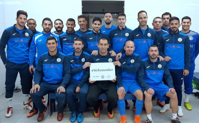 """שחקני קבוצת הבוגרים """"מכבי נווה שאנן אלדד"""" עם שלט הקמפיין """"אנחנו זוכרים""""."""